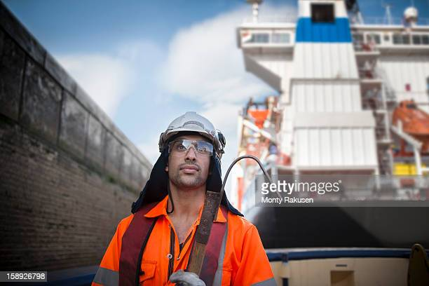portrait of tug worker wearing hard hat and protective goggles holding tool - monty rakusen stock pictures, royalty-free photos & images