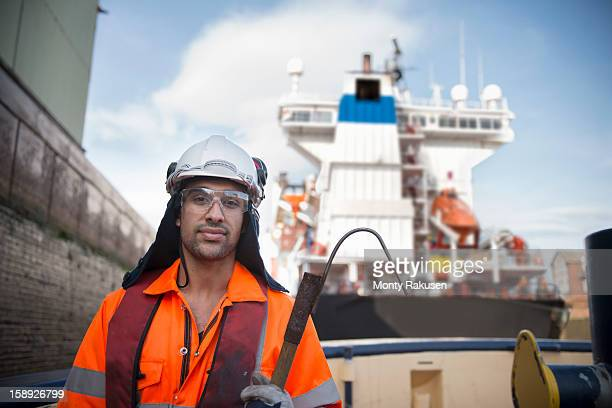 Portrait of tug worker wearing hard hat and protective goggles holding tool, looking at camera