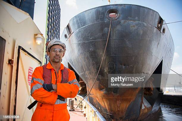 Portrait of tugboat worker in front of ship's bows in dock