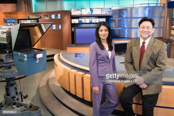 Portrait of TV news anchor people in newsroom