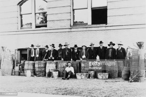 Portrait of twelve men, two with law enforcement badges, who stand behind of a row group of barrels, along with a thirteenth man who sits in front,...
