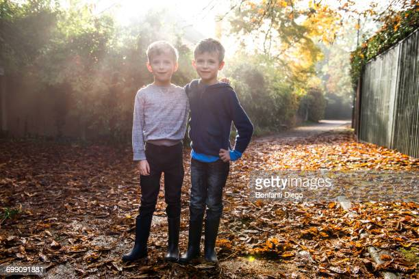 Portrait of twin boys, outdoors, surrounded by autumn leaves
