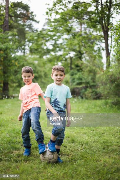 Portrait of twin boys standing with soccer ball at back yard