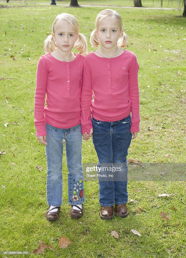 Portrait of twin sisters (6-7) in park : Stockfoto