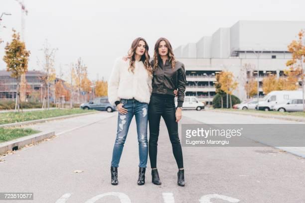 portrait of twin sisters, in urban area, standing side by side - calças justas - fotografias e filmes do acervo
