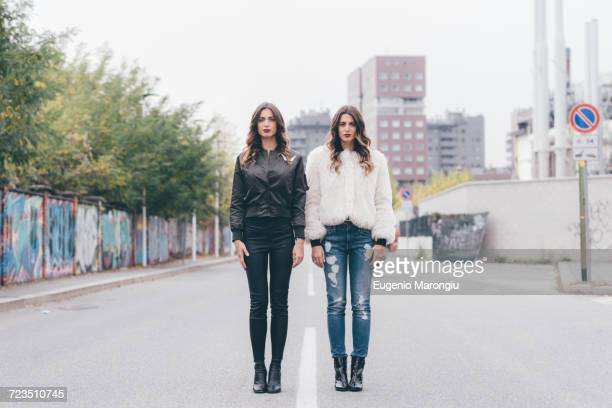 Portrait of twin sisters, in urban area, standing side by side