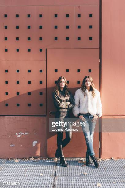 Portrait of twin sisters, outdoors, leaning against wall