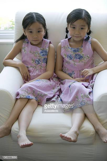 portrait of twin sisters sitting on an armchair - asian twins stock photos and pictures