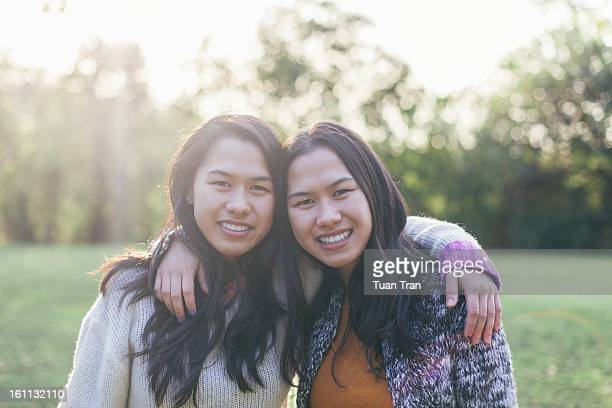 portrait of twin sisters smiling at the park - asian twins stock photos and pictures