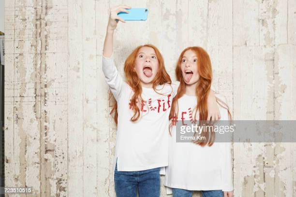 portrait of twin sisters wearing christmas jumpers, taking selfie using smartphone - redhead girl stock photos and pictures