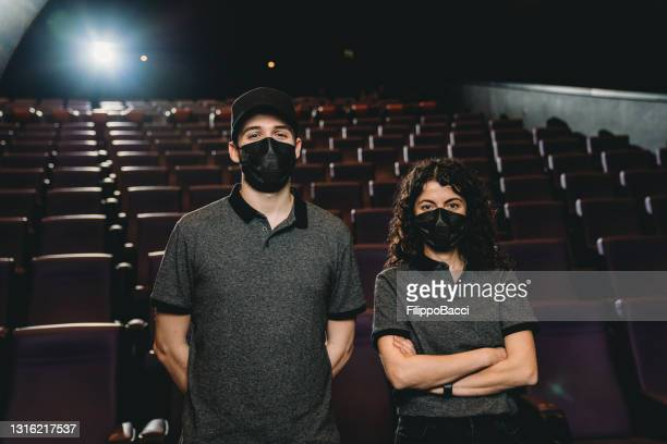 portrait of two adult cinema staff workers against seat rows - film festival stock pictures, royalty-free photos & images
