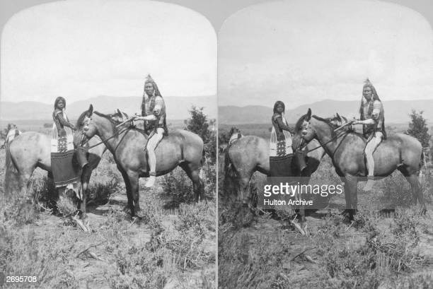 Portrait of two American Indians one adult and one child sitting on horses that face in opposite directions Photograph taken from a stereoscopic print