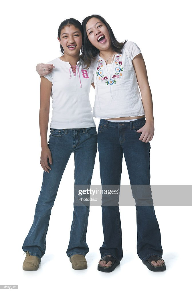 portrait of two asian sisters in jeans and white shirts as they put their arms around each other and smile : Foto de stock
