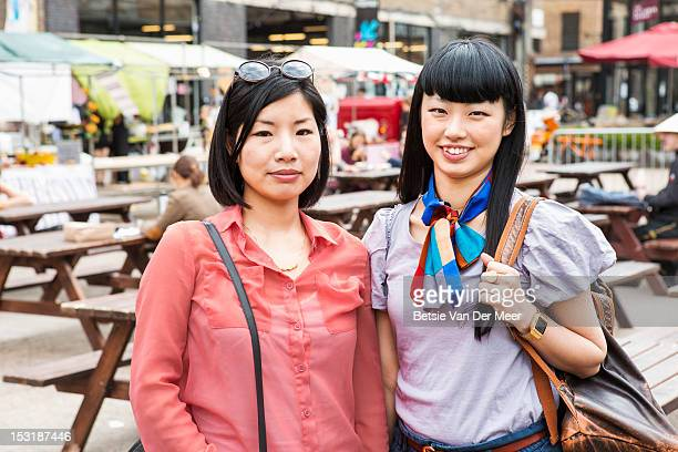 Portrait of two asian women at urban market.