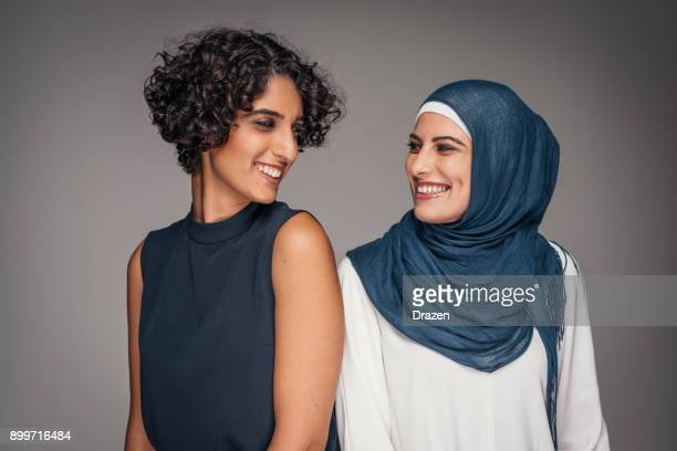 portrait of two beautiful women from middle east who live and work in australia - contrasti foto e immagini stock