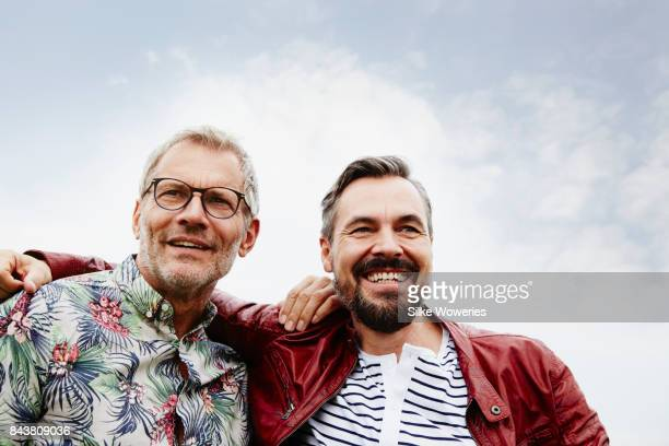 portrait of two best buddies embracing their friendship - male friendship stock pictures, royalty-free photos & images