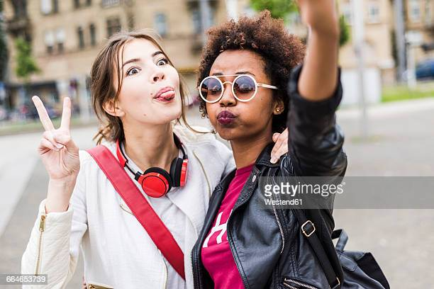 Portrait of two best friends pulling funny faces while taking selfie