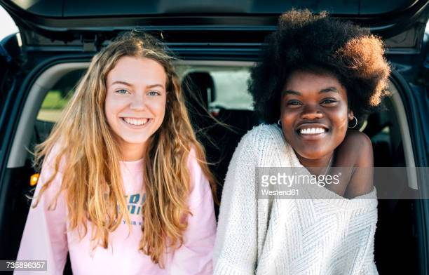 portrait of two best friends sitting in a car - close to stock pictures, royalty-free photos & images