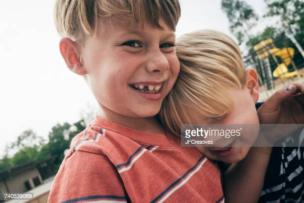 Portrait of two boys in playground, smiling