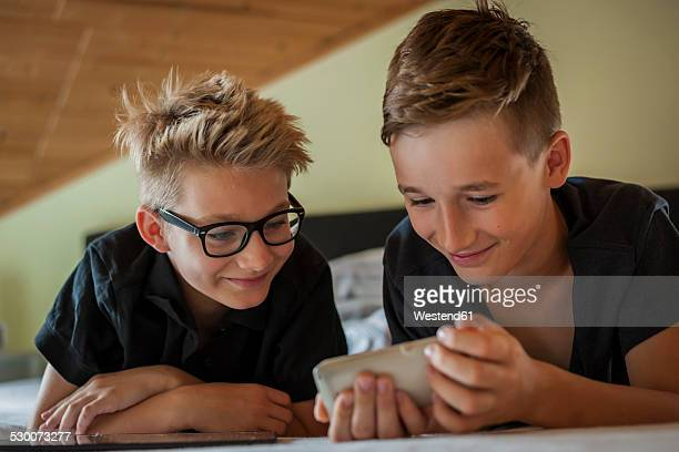 Portrait of two boys lying on bed using smartphone