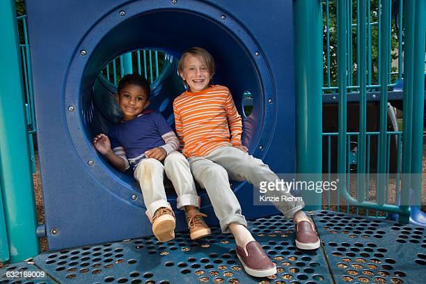 portrait of two boys sitting in playground tunnel - 6 7 anni foto e immagini stock