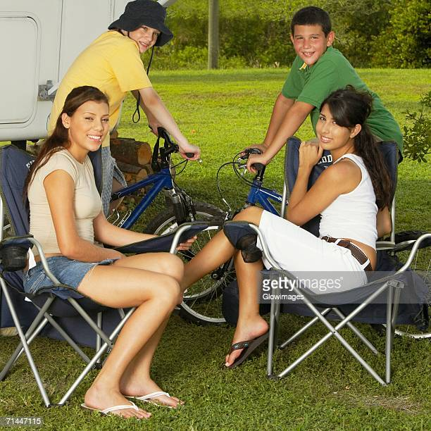 Portrait of two boys sitting on bicycles with two teenage girls sitting on armchairs and smiling