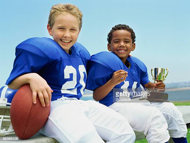 portrait of two boys sitting with a football and a trophy - american football uniform stock pictures, royalty-free photos & images