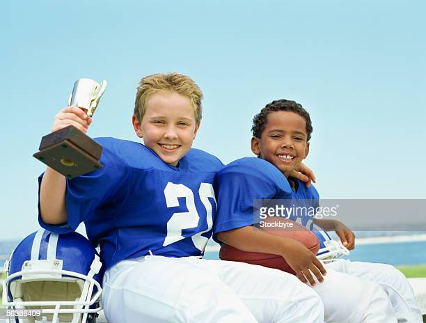 portrait of two boys sitting with a football and a trophy