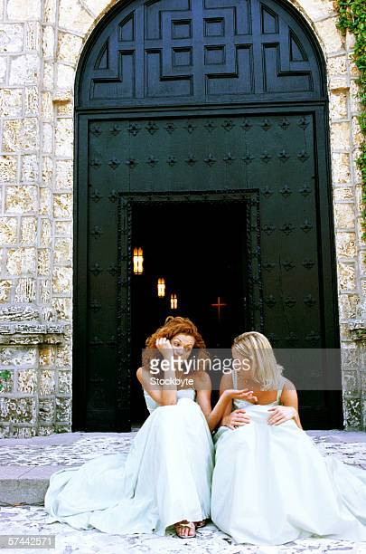 portrait of two bridesmaid sitting on the steps outside a church