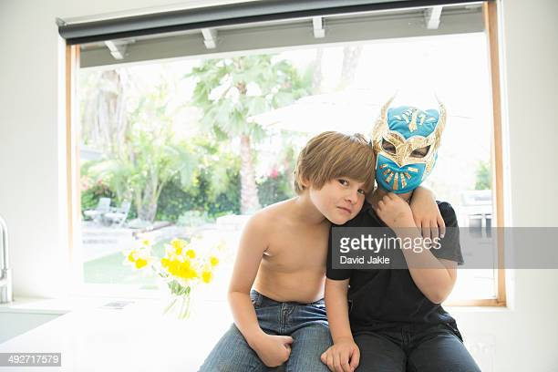 Portrait of two brothers, one bare chested and one masked