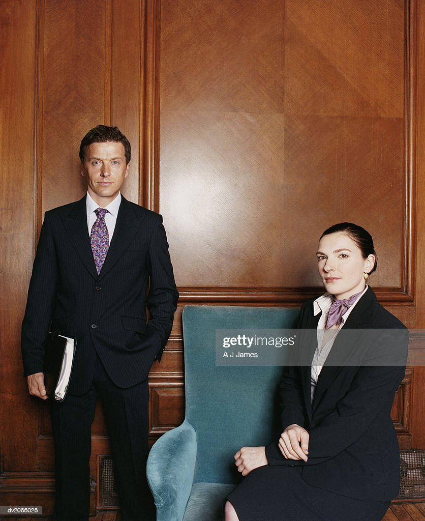 Portrait of Two Business Executives Around an Armchair : Stock Photo