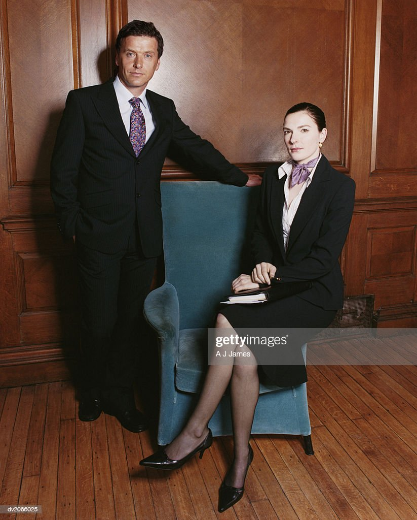 Portrait of Two Business Executives by an Armchair : Stock Photo
