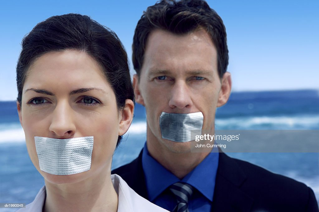 Portrait of Two Business Executives Standing on a Beach With Duct Tape Covering Their Mouths : Stock Photo