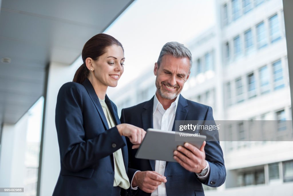Portrait of two business partners looking together at tablet : Stock Photo