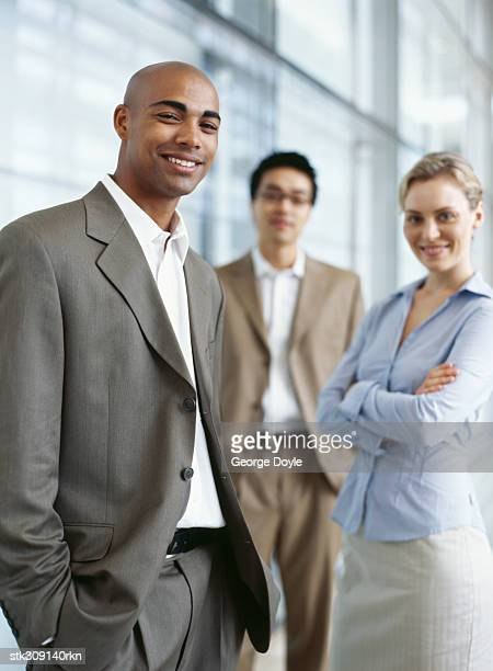 portrait of two businessmen and a businesswoman standing in an office