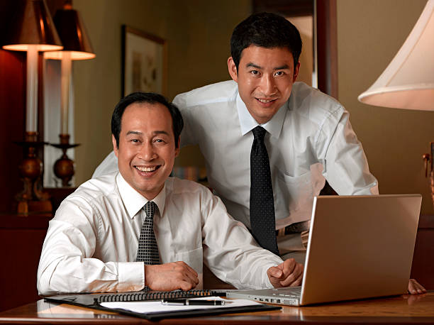 Portrait of two businessmen at laptop.