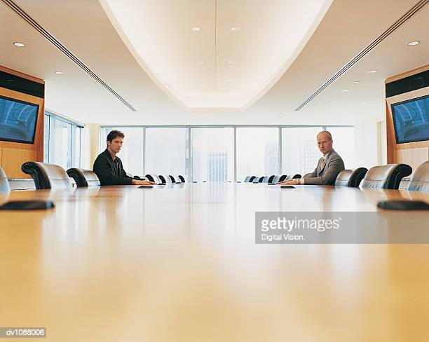 Portrait of Two Businessmen Sitting Opposite Each Other Across a Conference Room Table