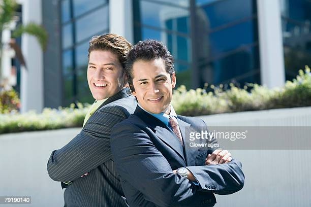 Portrait of two businessmen standing back to back and smiling