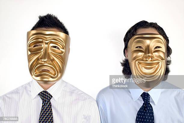 portrait of two businessmen wearing gold tragedy and comedy drama masks - 悲劇の面 ストックフォトと画像