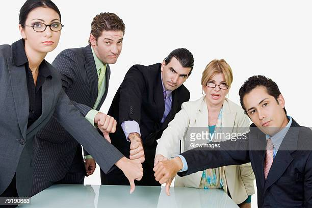 portrait of two businesswomen and three  businessmen showing thumbs down sign - dismissal stock photos and pictures