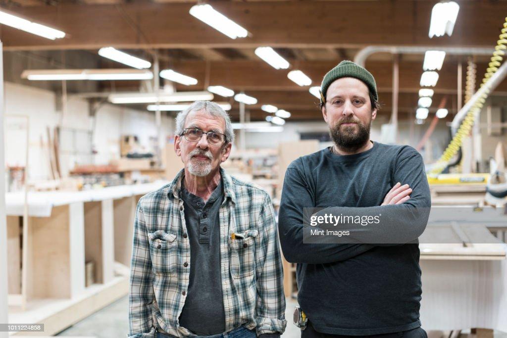 Portrait of two Caucasian carpenters in a large woodworking factory. : Foto de stock