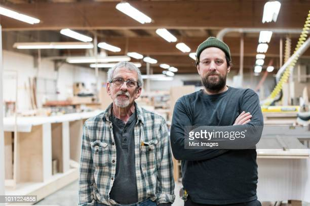 Portrait of two Caucasian carpenters in a large woodworking factory.
