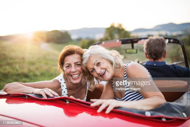 A portrait of two cheerful senior women sitting in cabriolet on a road trip in summer at sunset.