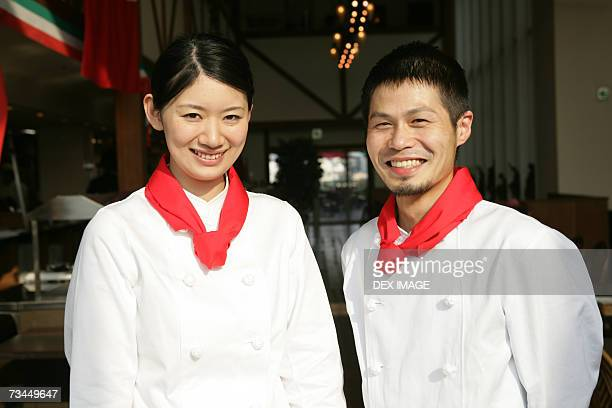 portrait of two chefs standing in a restaurant and smiling - ネッカチーフ ストックフォトと画像