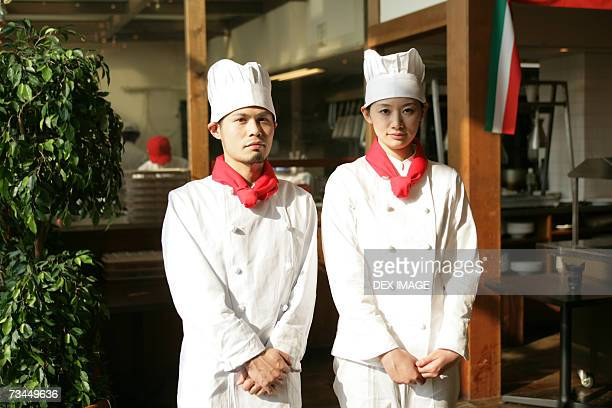 portrait of two chefs standing in front of a restaurant - ネッカチーフ ストックフォトと画像