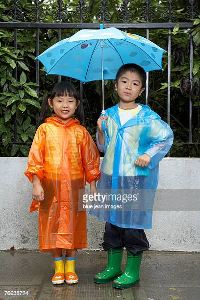 Portrait of two children in their raincoats.