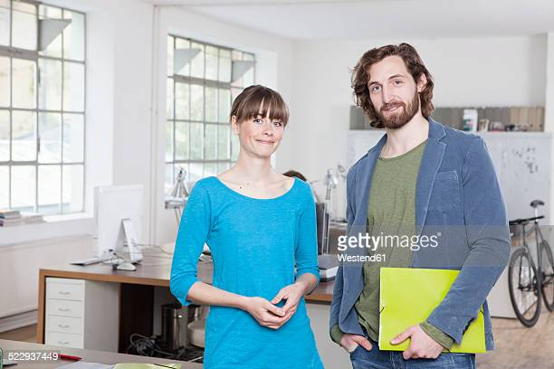 Portrait of two colleagues standing in an office