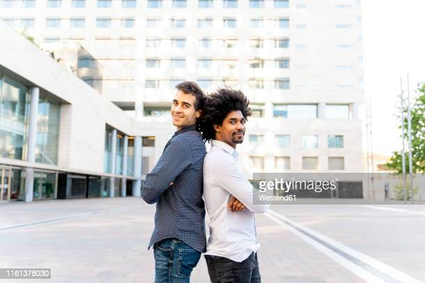portrait of two confident businessmen standing back to back in the city, barcelona, spain - 背中合わせ ストックフォトと画像