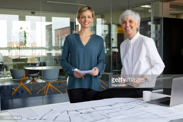 portrait of two confident businesswomen with construction plan in office - 女性建築家 ストックフォトと画像