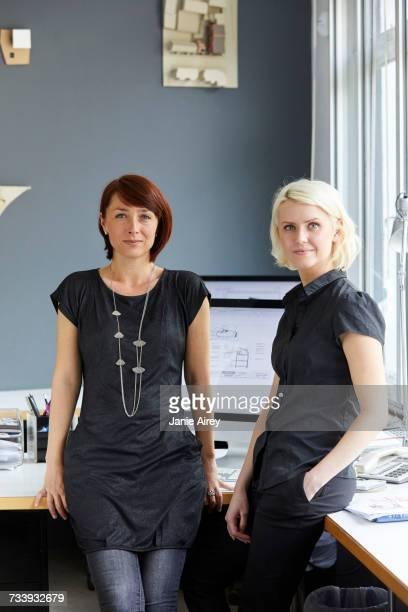 Portrait of two confident female designers at office desk